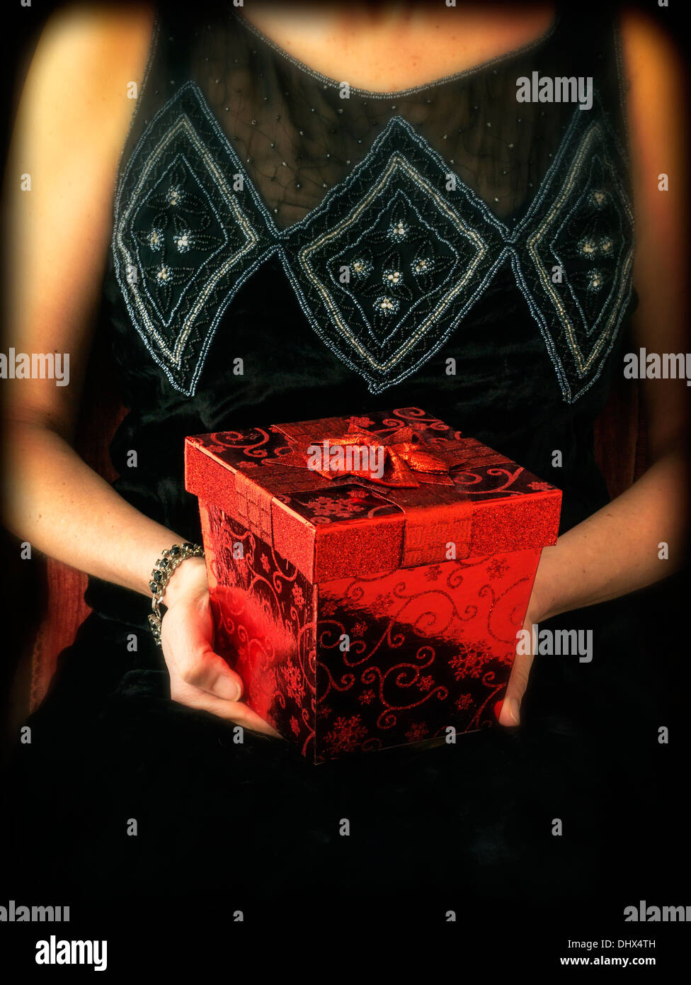 A cropped woman in a period dress holding a fancy red gift box Stock Photo