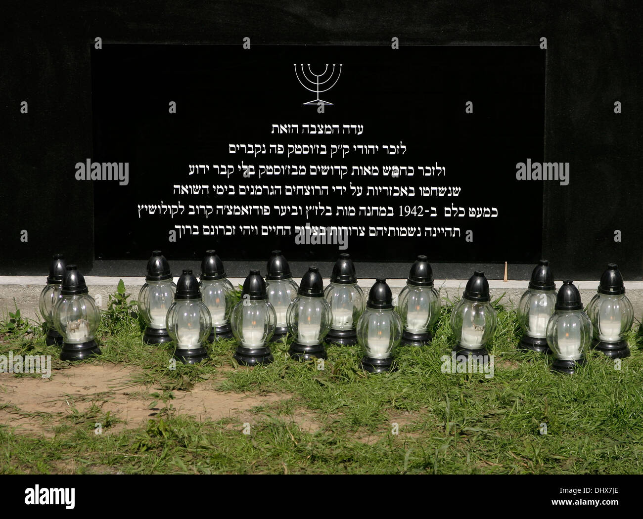 Hebrew inscription on memorial stone in Brzostek Jewish cemetery Poland, memorial lamps placed in front of stone - Stock Image