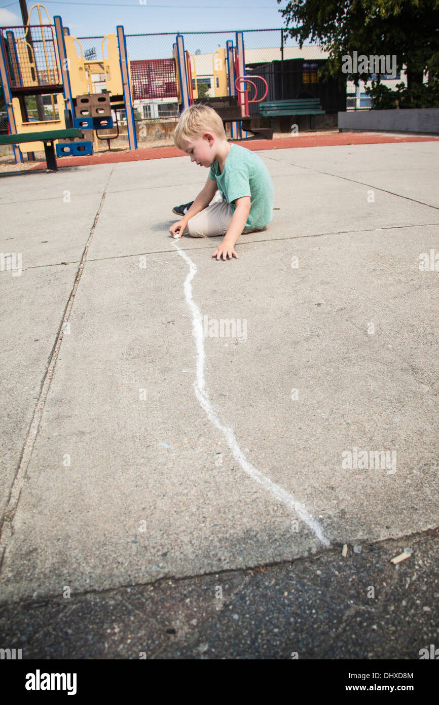 Boy Drawing Straight Line with Chalk on Playground - Stock Image