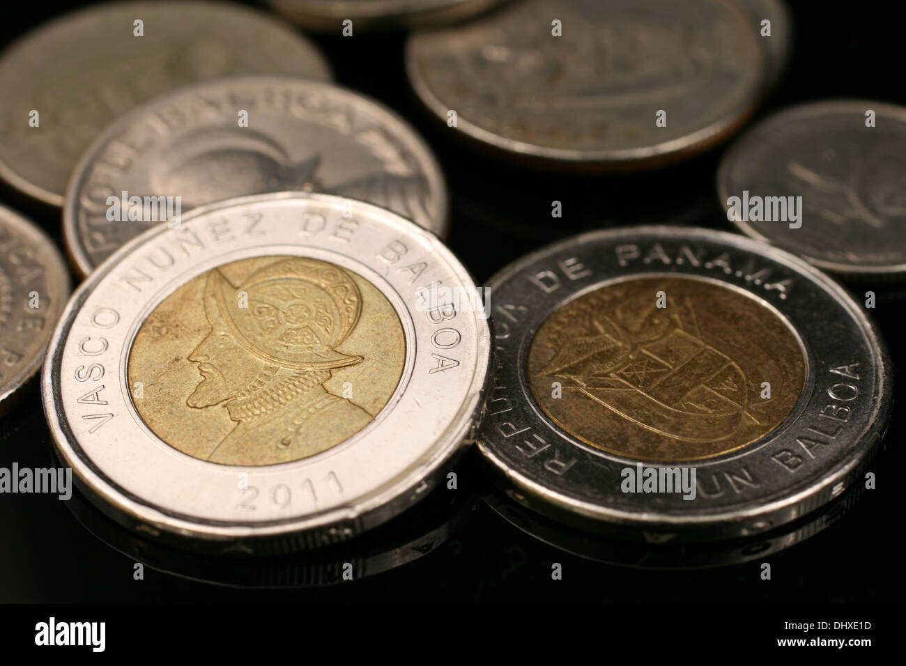 A close up image of panamanian coins on a black background - Stock Image
