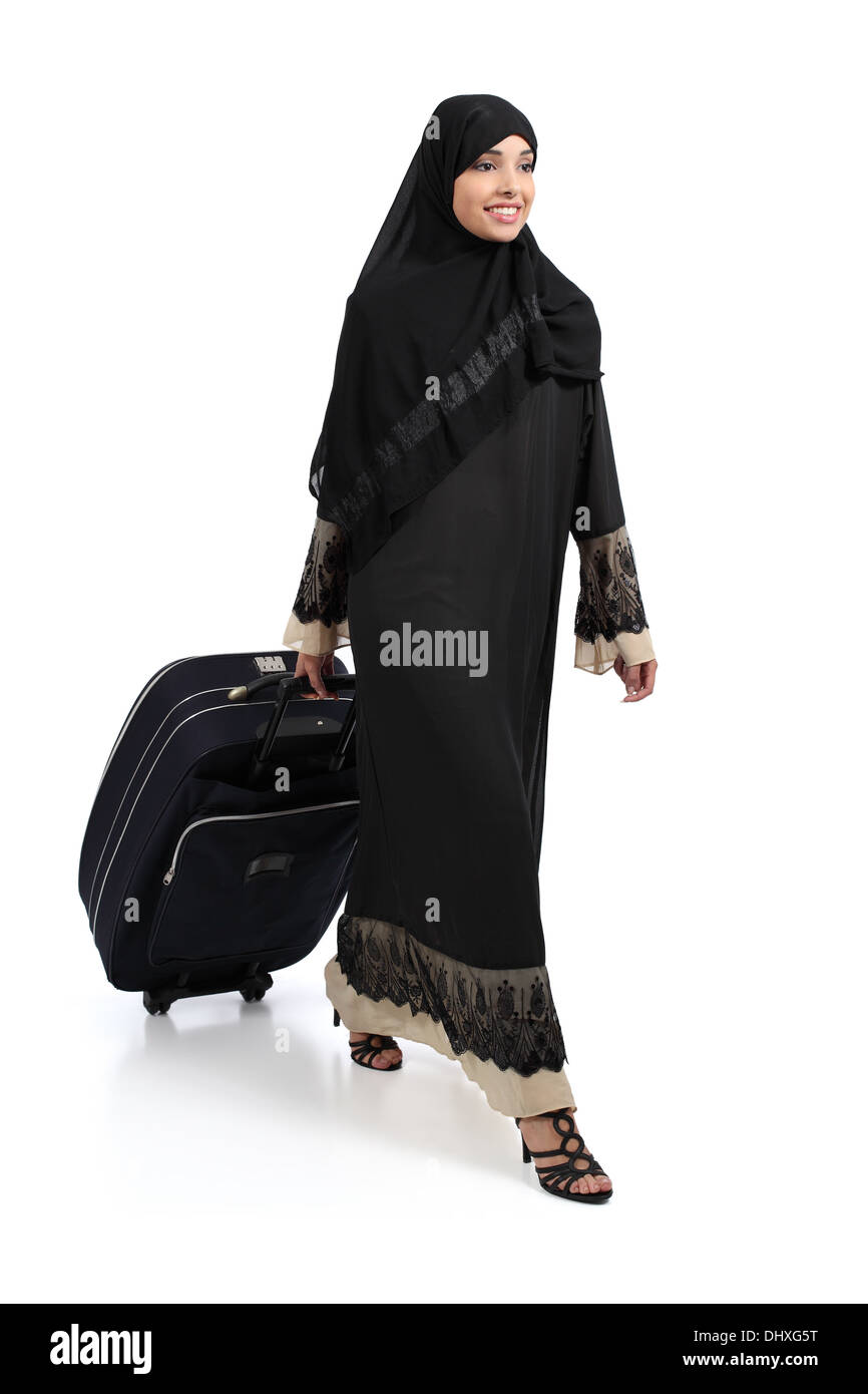 Arab woman walking carrying a suitcase isolated on a white background - Stock Image