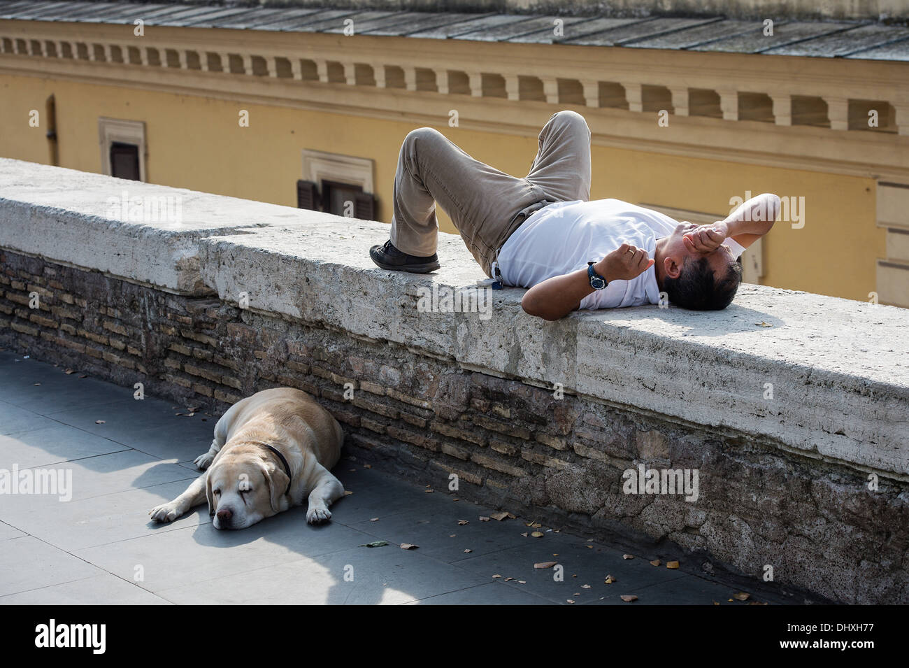 Man and dog take an afternoon break, Rome, Italy - Stock Image