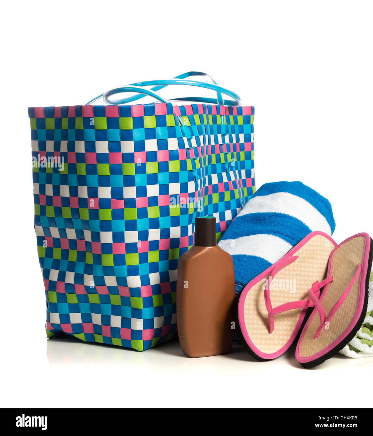 A beach bag with a striped towel, suntan lotion and pink flip-flops on a white background - Stock Image