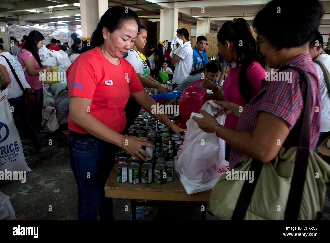 International Convention Centre,Cebu City 16/11/2013. A Cebu City initiative involving a number of Government Agencies in the aftermath of Typhoon Haiyan/Yolanda. A 24hr relief aid operation involves the receiving and re-packing of food items destined for the hardest hit areas. Volunteers are mainly students. Relief packs contain 6 kilos of rice,5 tins of sardines,5 tins of corned beef/beef loaf. - Stock Image
