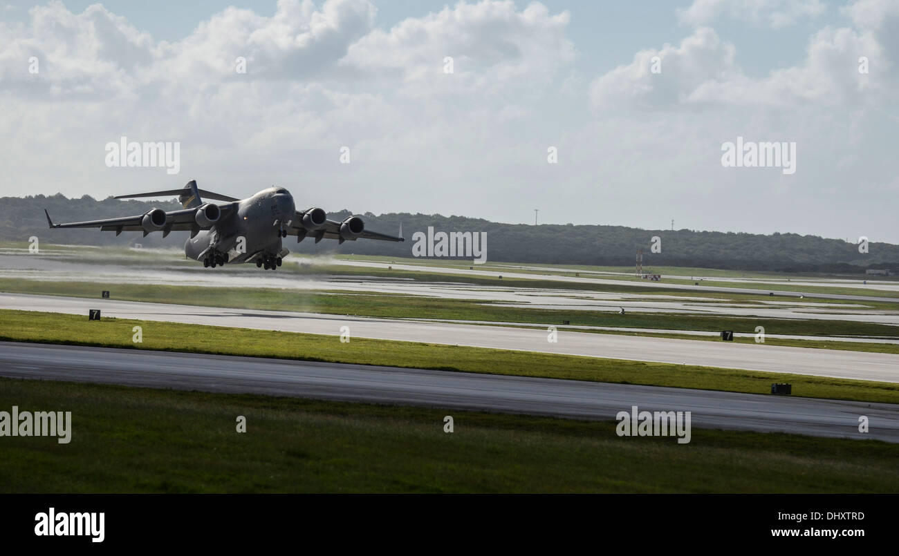 A C-17 Globemaster III takes off from the Andersen Air Force Base, Guam, flightline to support Operation Damayan in Tacloban, Philippines. Operation Damayan is a U.S. humanitarian aid and disaster relief effort to support the Philippines in the wake of th - Stock Image