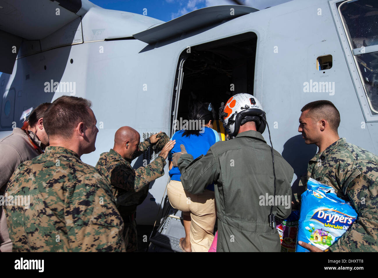 Marines with Marine Medium Tiltrotor Squadron 262, 1st Marine Air Wing, assist a Filipino woman and her pre-mature Stock Photo
