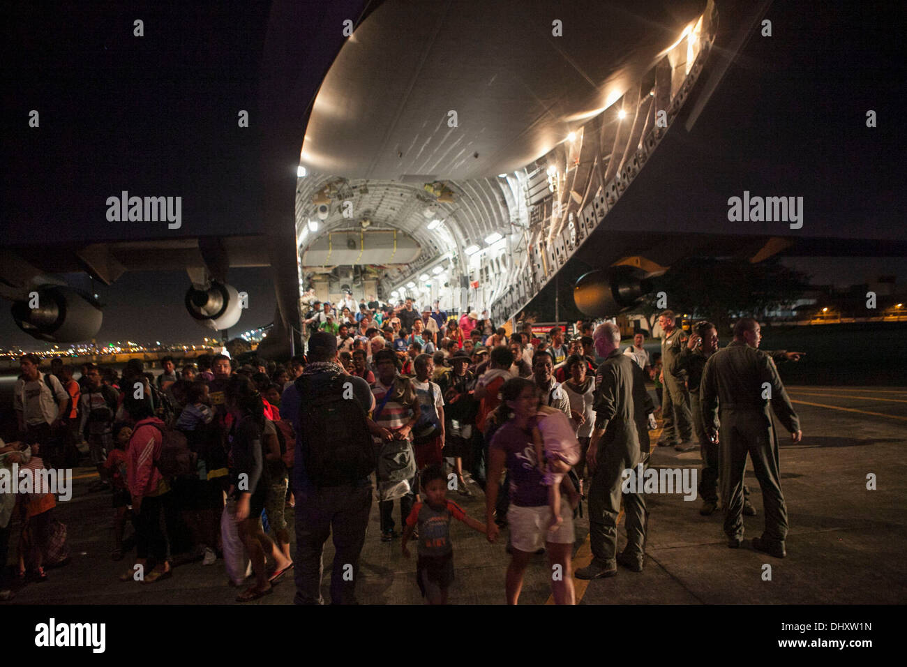 Displaced Filipinos and other international personnel offload from a C-17 Globemaster III with the 535th Air Lift Squadron out o - Stock Image