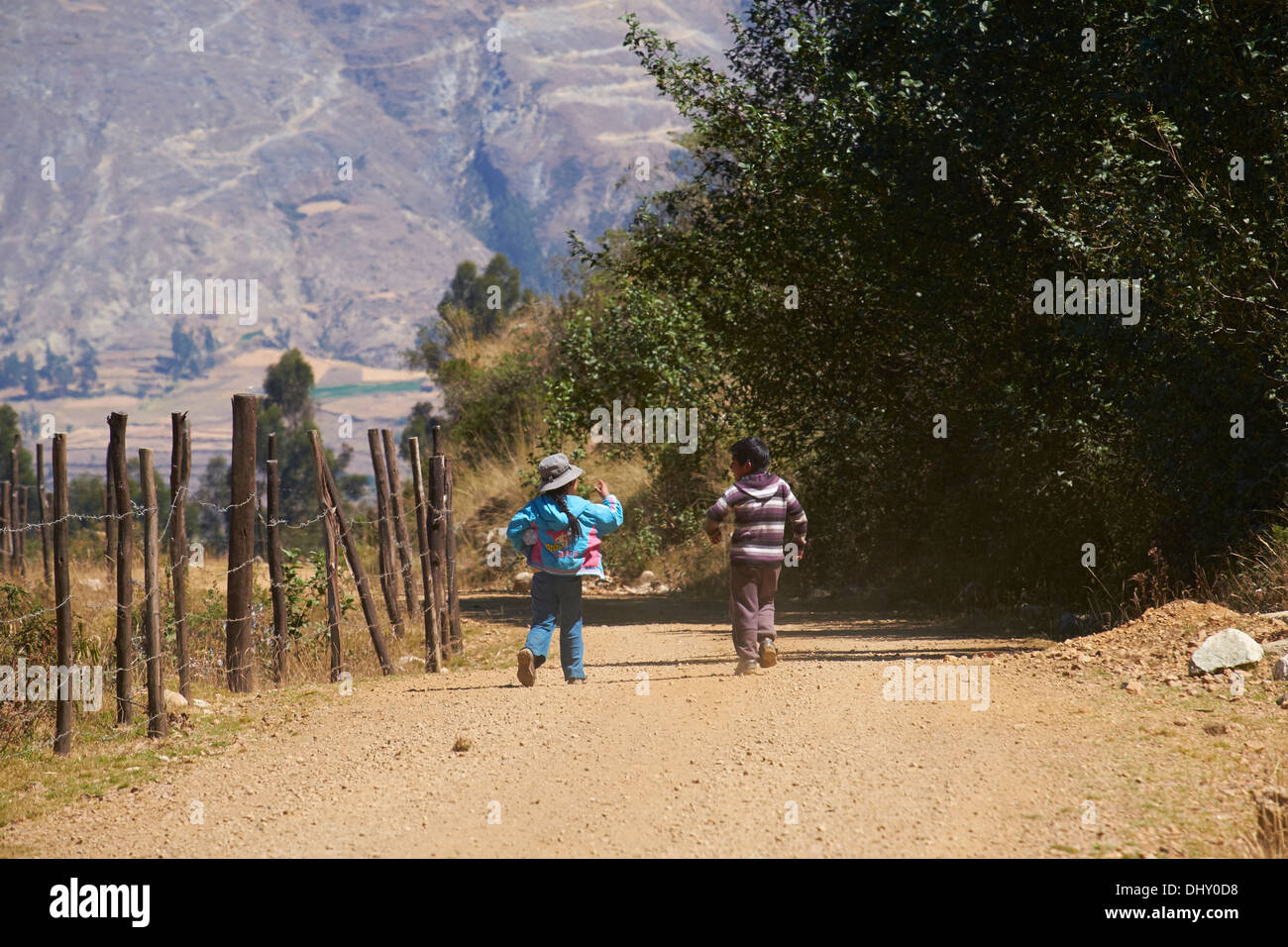 Young children playing,skipping down the road in the Peruvian Andes. - Stock Image