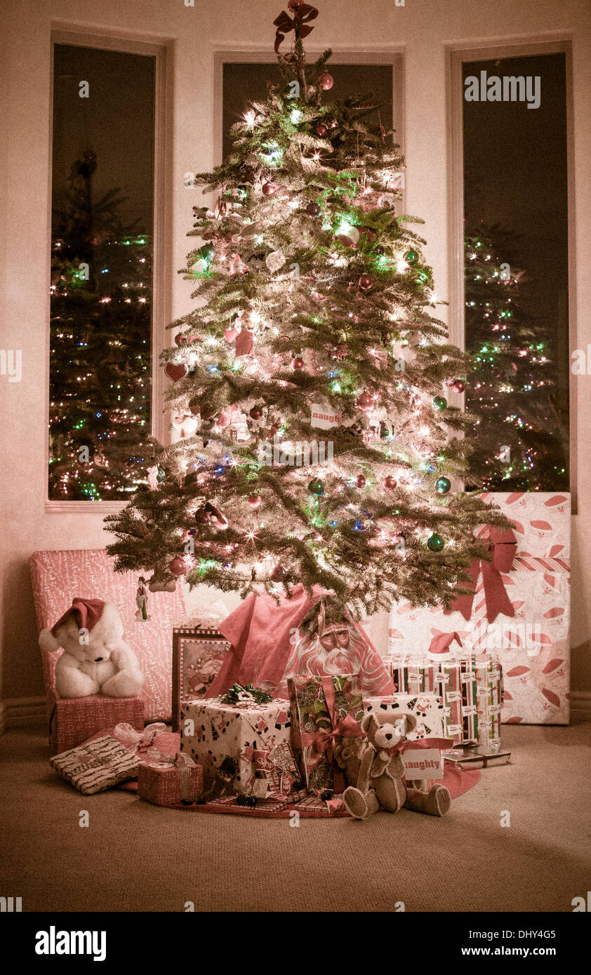 Beautiful Christmas tree surrounded by presents lit up at night ...