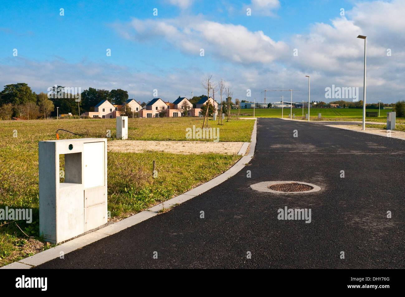 Concrete electricity meter units on unbuilt housing estate site - France. Stock Photo