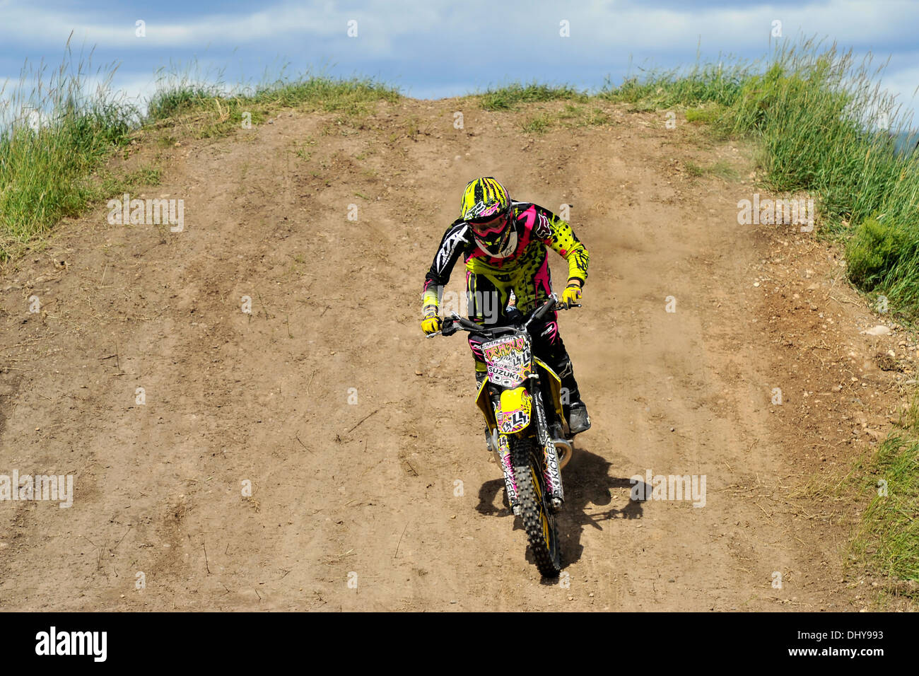 A motocross bike rider  riding down a hill on a gravel track - Stock Image