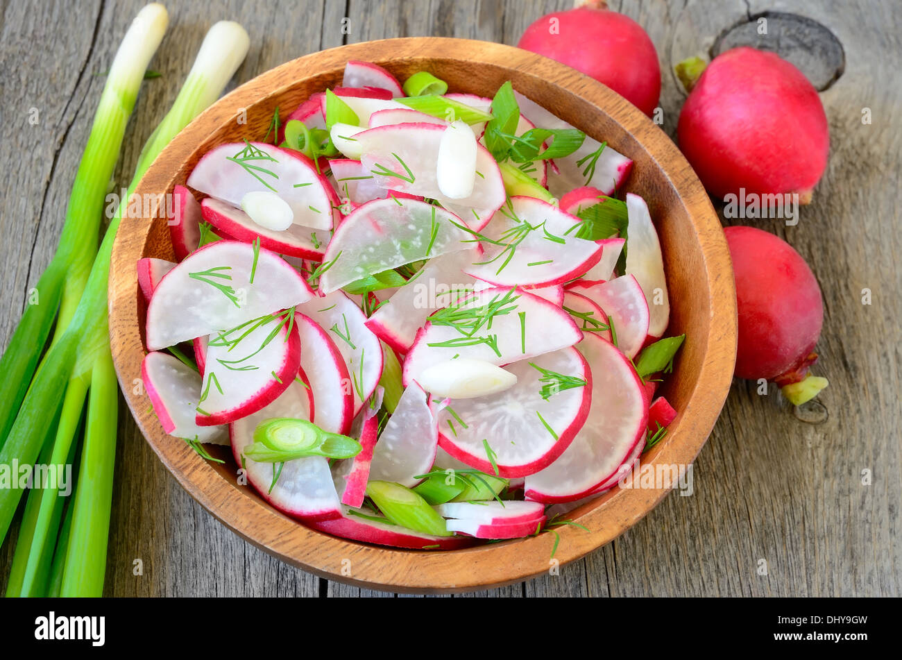 Radish salad in brown bowl on wooden table - Stock Image