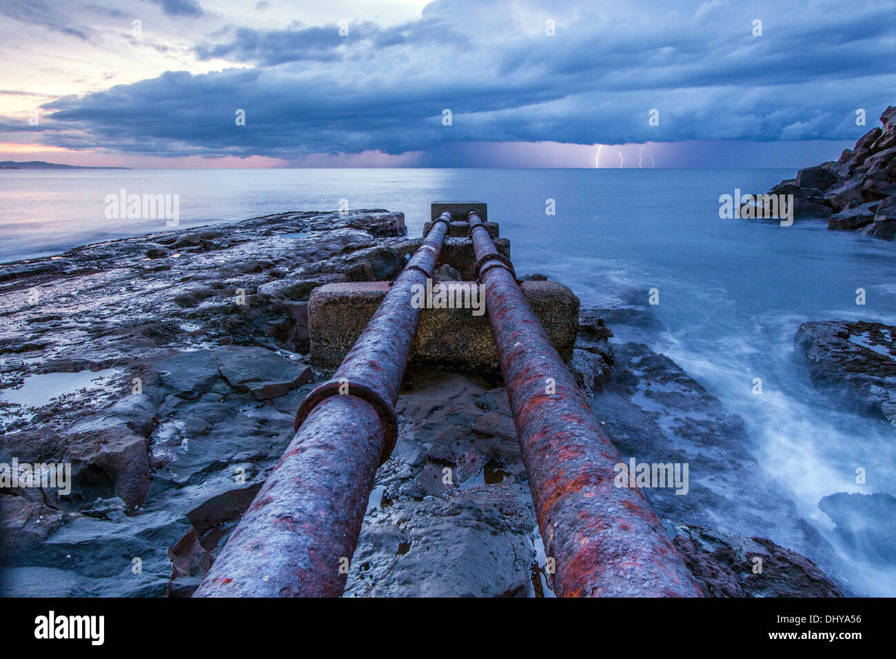 Pipes heading into the ocean with lightening in background - Stock Image