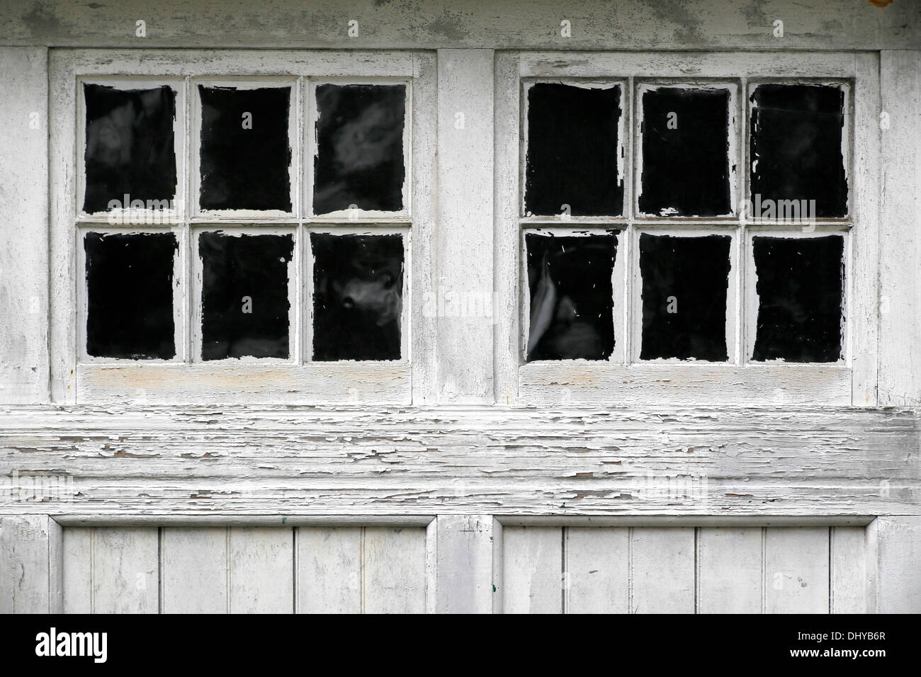Weather beaten old garage doors, sloppily painted around the window panes. - Stock Image