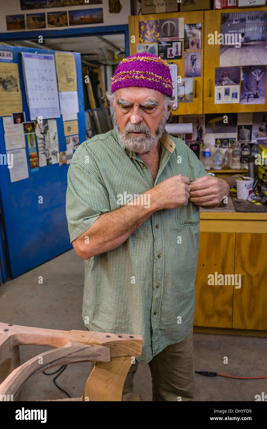 Larry White, fine woodworker, stands by a chair he is creating in the shop of the famous artist/woodworker Sam Maloof. Stock Photo