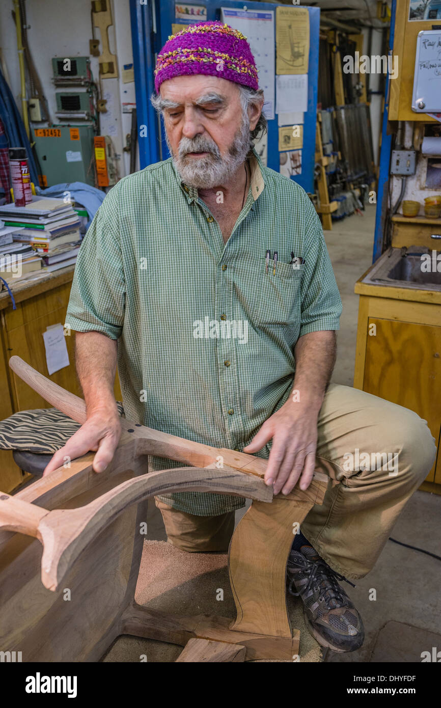 Larry White, fine woodworker, stands by a chair he is creating in the shop of the famous artist/woodworker Sam Maloof. - Stock Image