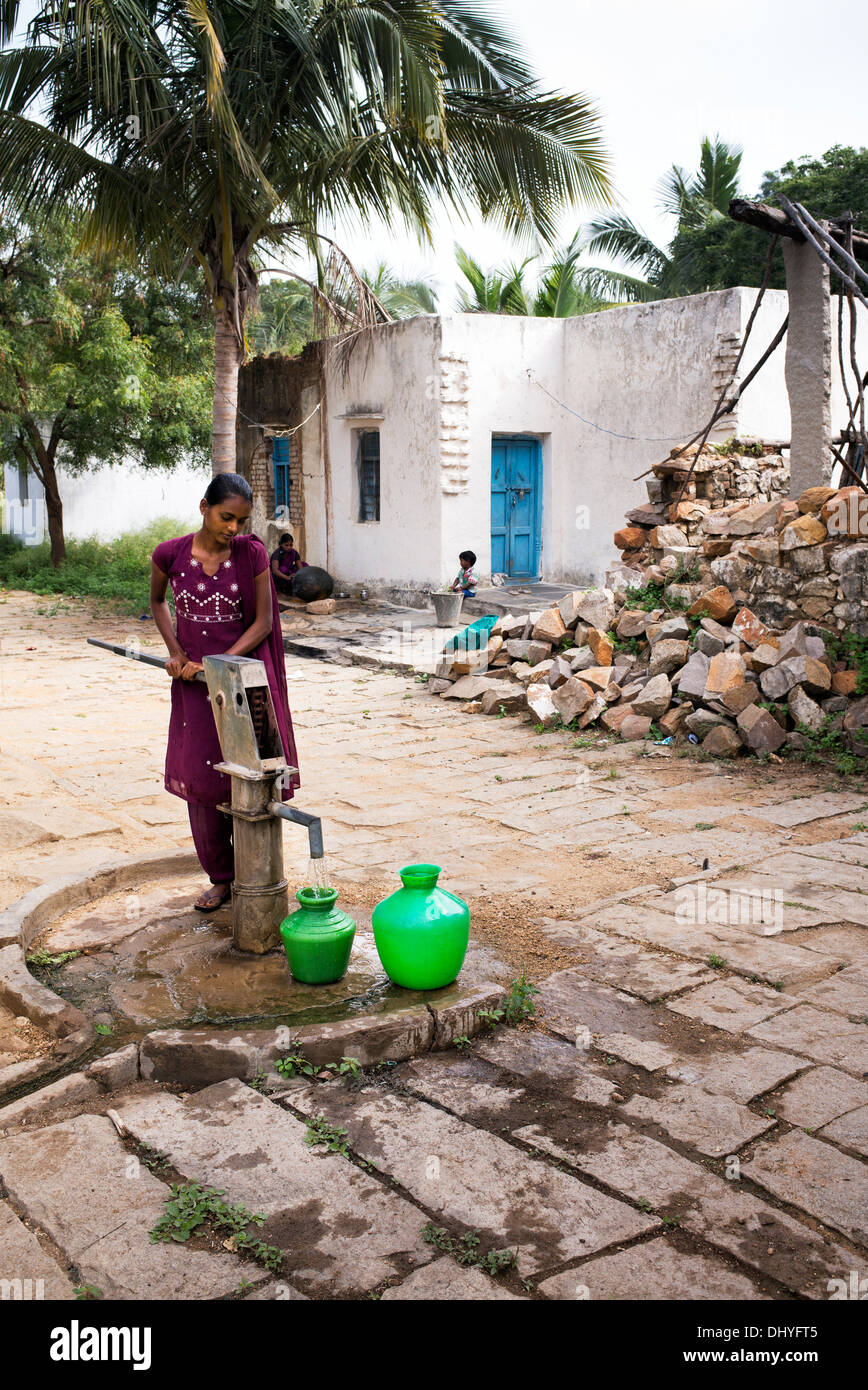 Indian teenage girl pumping water from a hand pump into a pot in a rural Indian village. Andhra Pradesh, India. - Stock Image