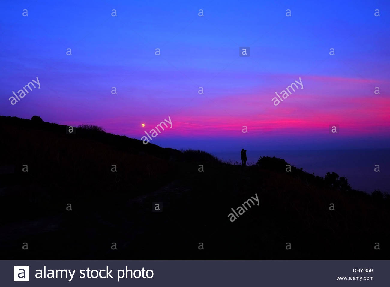A full moon at sunset over Fairlight Country Park in East Sussex, UK - Stock Image
