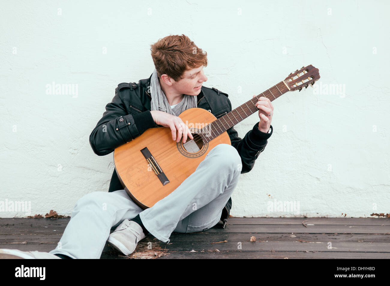 Handsome young man playing acoustic guitar - Stock Photo