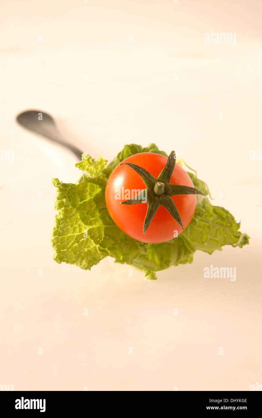 Fork with pinned lettuce and cherry tomato on white background - Stock Image