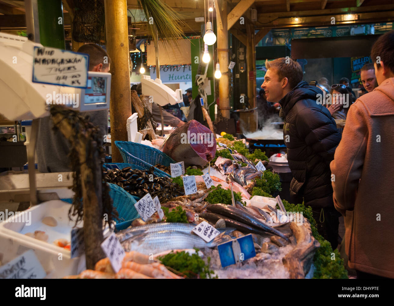 People shopping at busy wet fish stall in Borough Market Southwark London SE1 UK - Stock Image