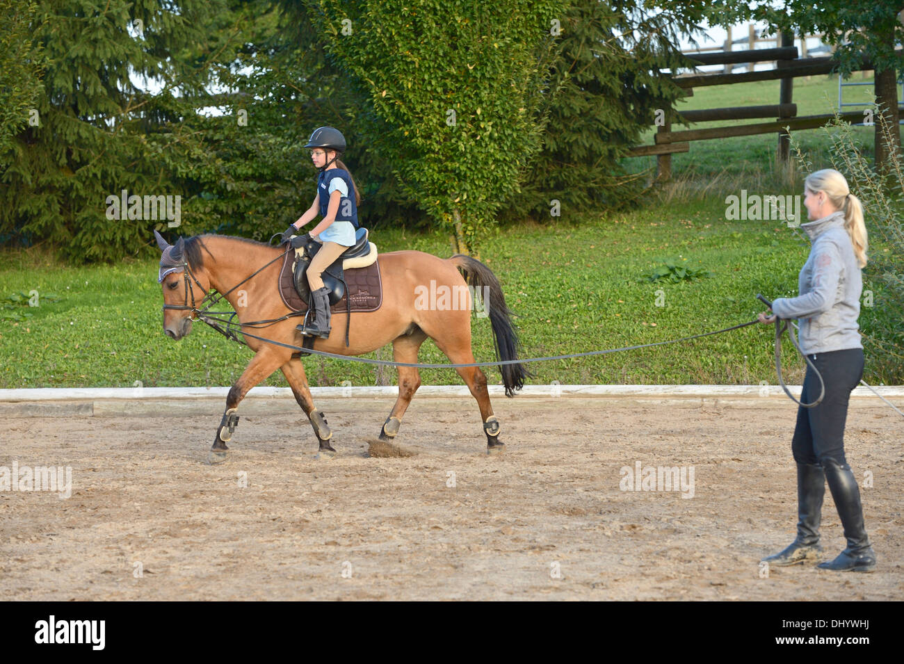 Girl wearing a body protector having a lunge lesson on back of a pony trotting - Stock Image
