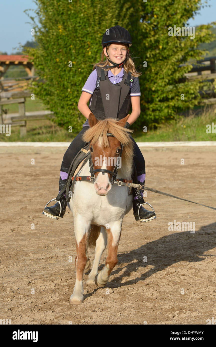Girl wearing a body protector having a lunge lesson on pony trotting - Stock Image