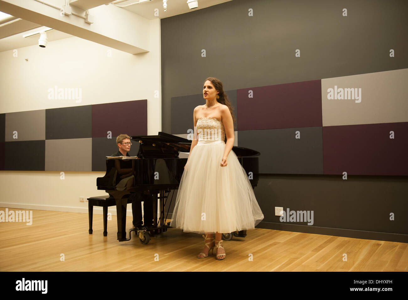 A student singing at a recital in a rehearsal room on Seventh Avenue in Manhattan. - Stock Image