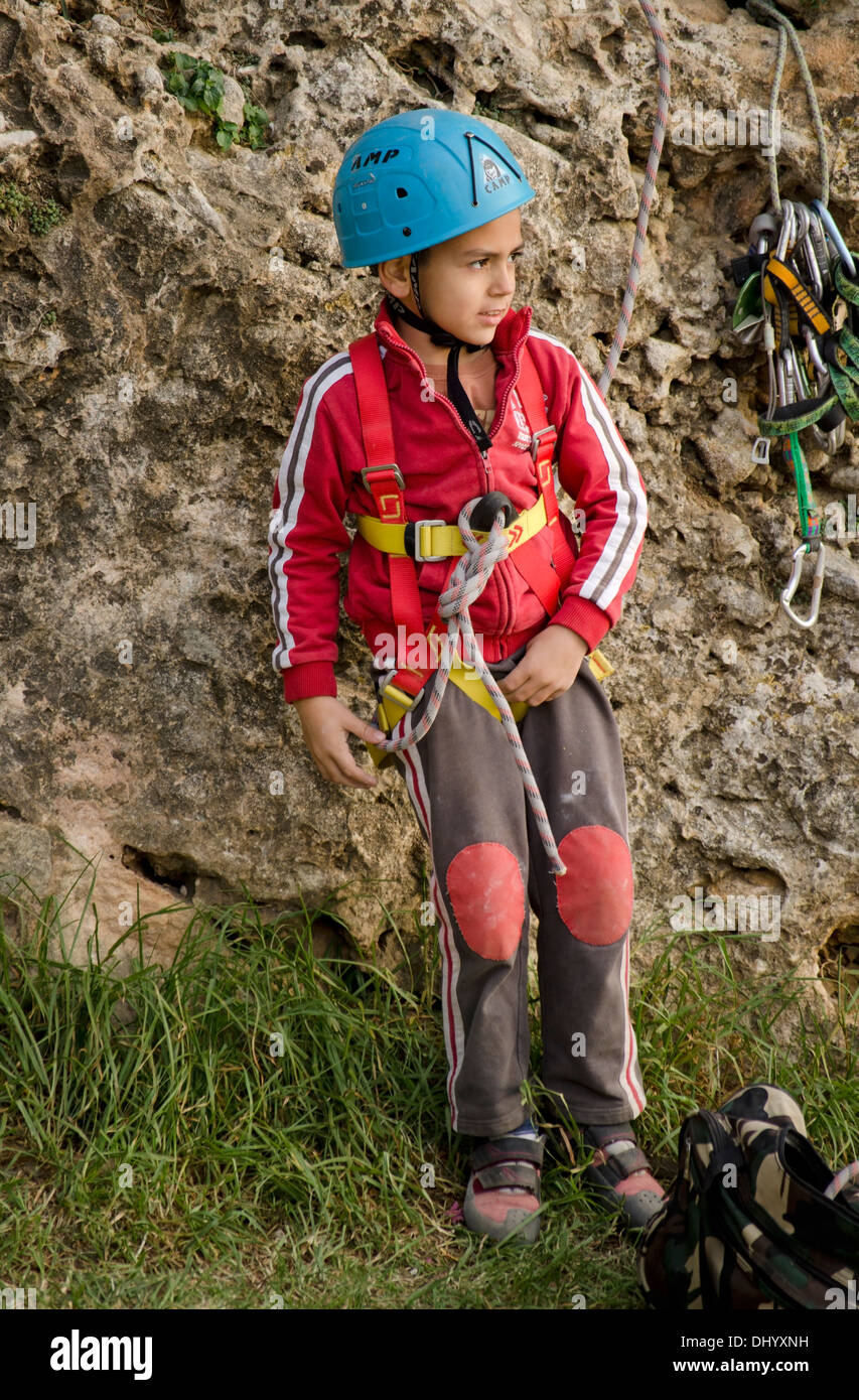 a young boy in front of a rock wall preparing for rock climbing in DHYXNH boy climbing wall harness helmet stock photos & boy climbing wall