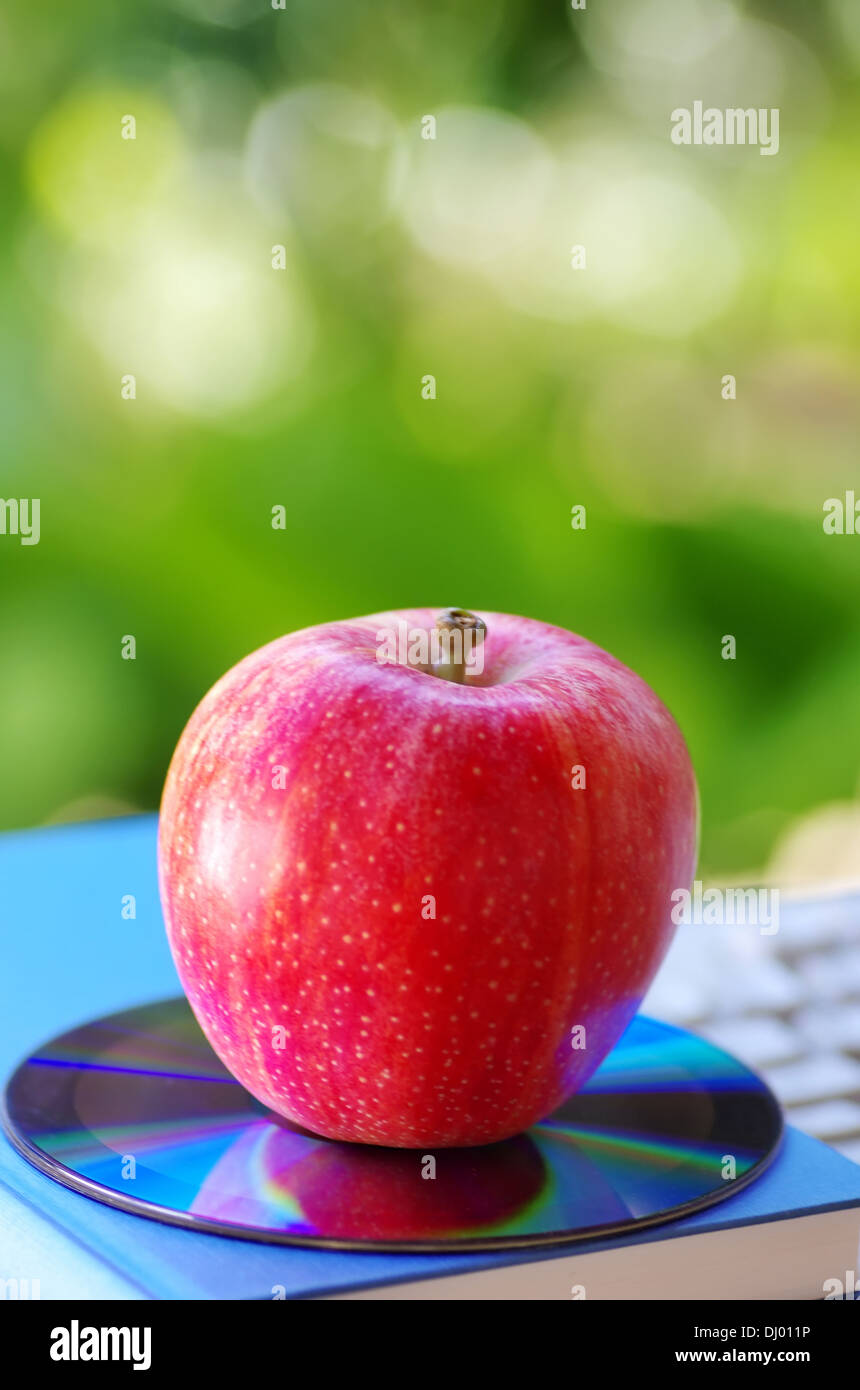 Red apple and DVD on books - Stock Image