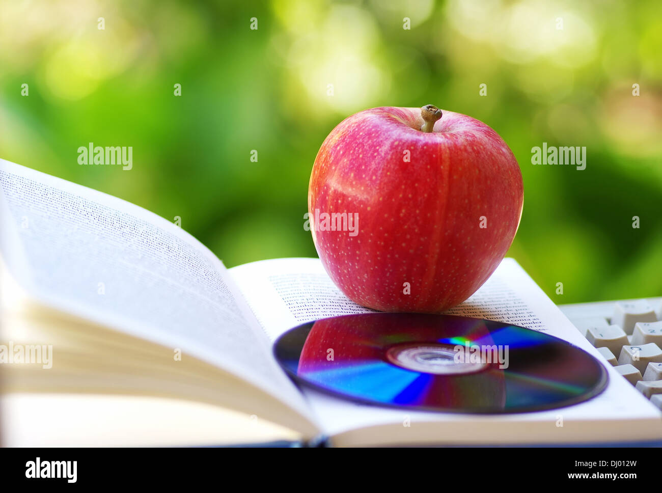 Ripe apple, dvd, and open book - Stock Image