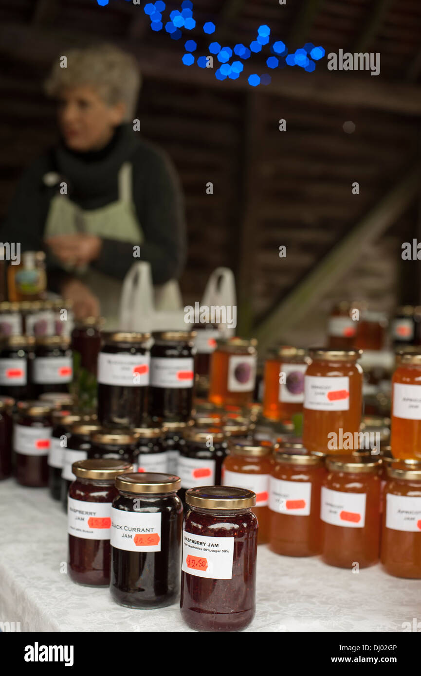 female stallholders at xmas fair selling home produced jams and preserves showing stallholder and blue xmas lights OOF in back - Stock Image