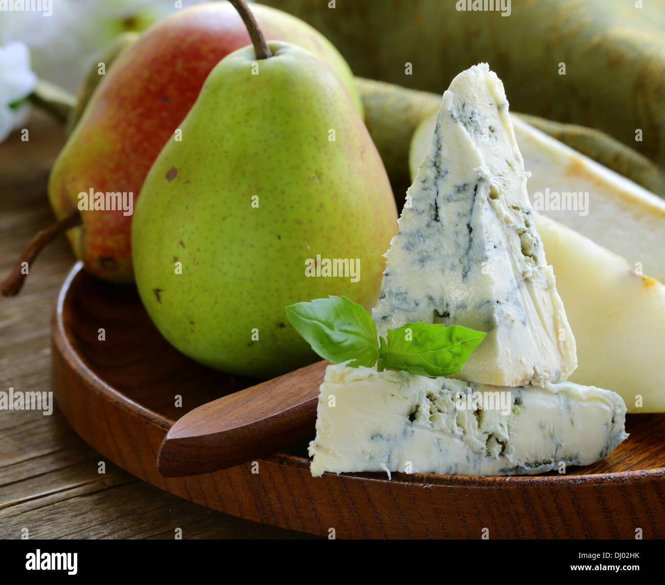Blue cheese and pears on a wooden plate - Stock Image