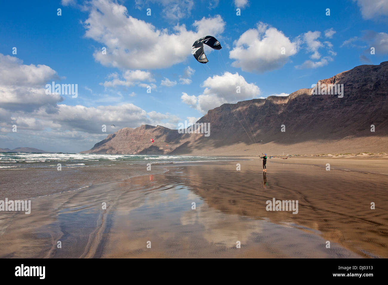 man kite surfing on windy famara beach with risco de famara in the background - Stock Image
