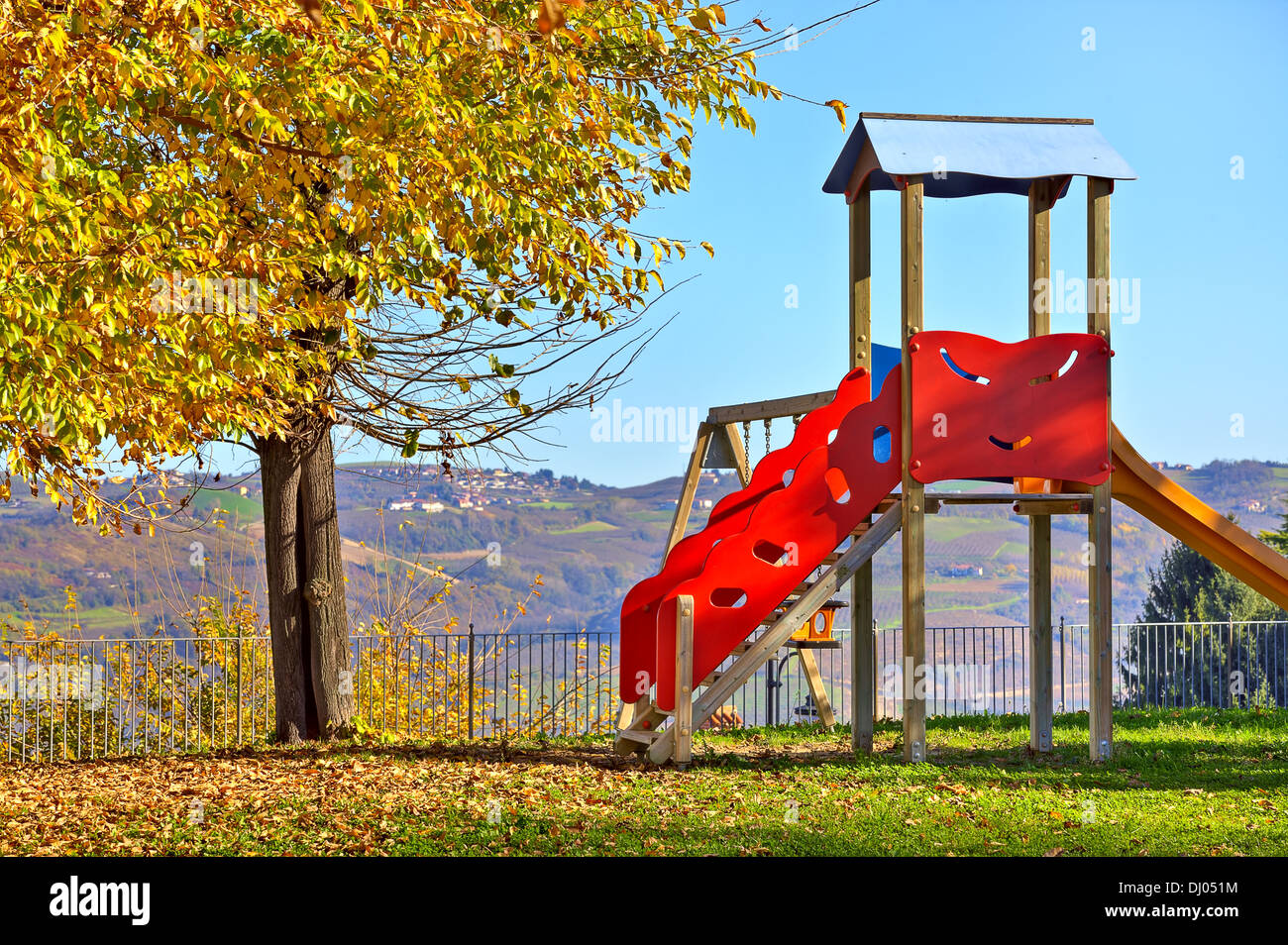 Lone children's slide on empty playground in autumn in small town of Diano D'Alba, Italy. - Stock Image