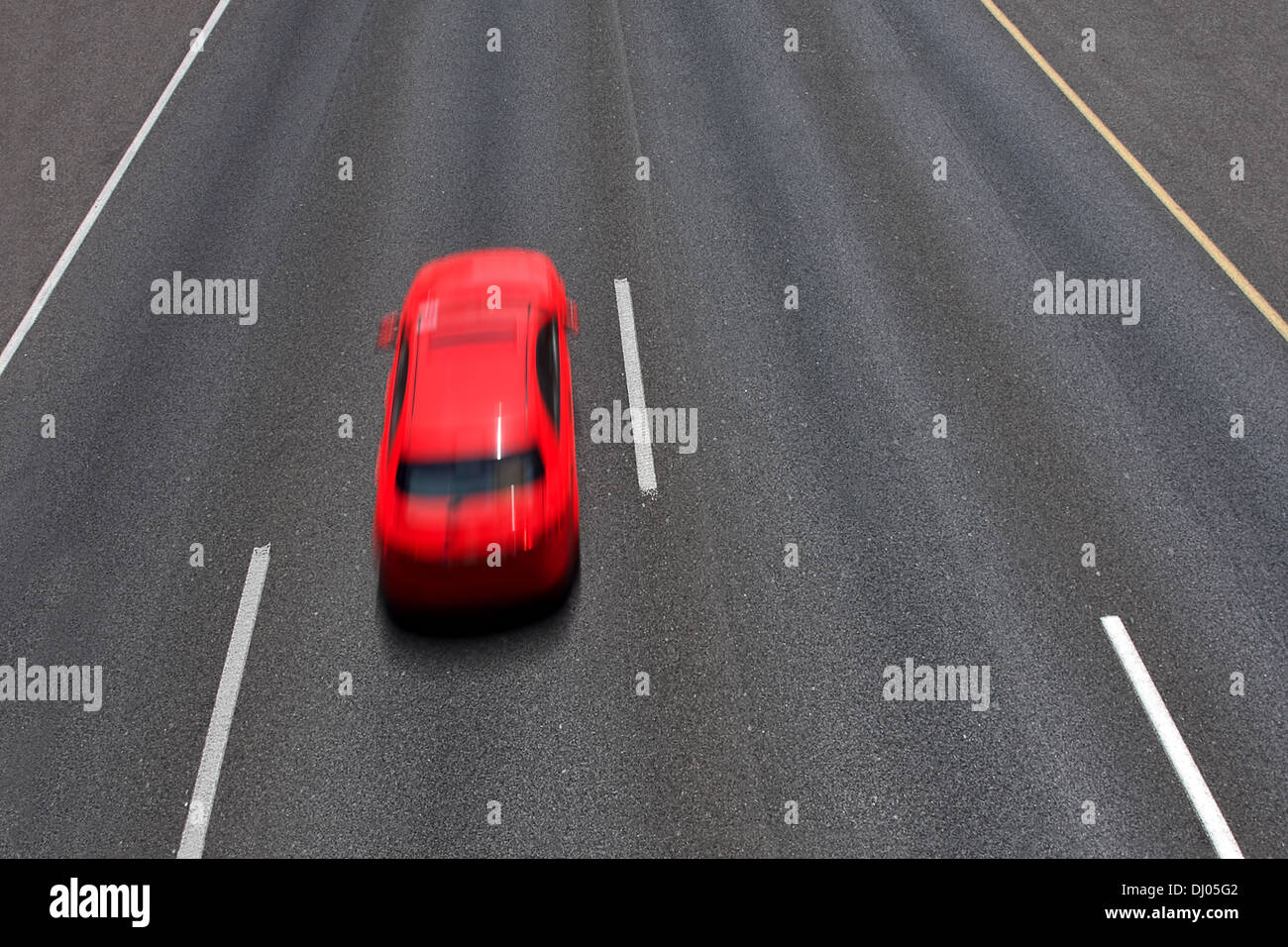 Red car moves fast on empty multilane highway ( long exposure, motion blurred, view from above). - Stock Image