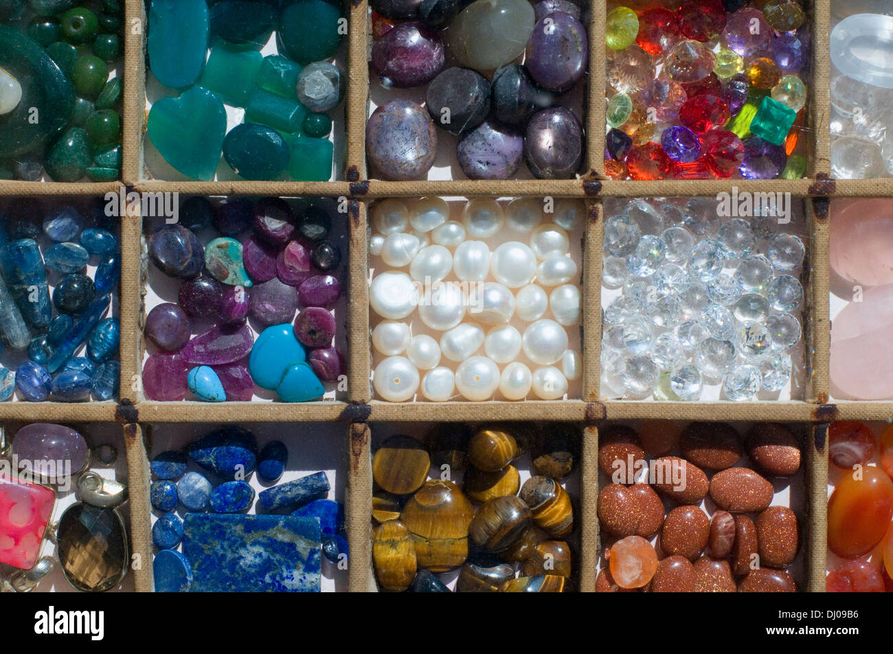 Semi precious stone for sale in their little boxes. Tigers eye, lapiz, pearls, smoky quartz, crystal - Stock Image