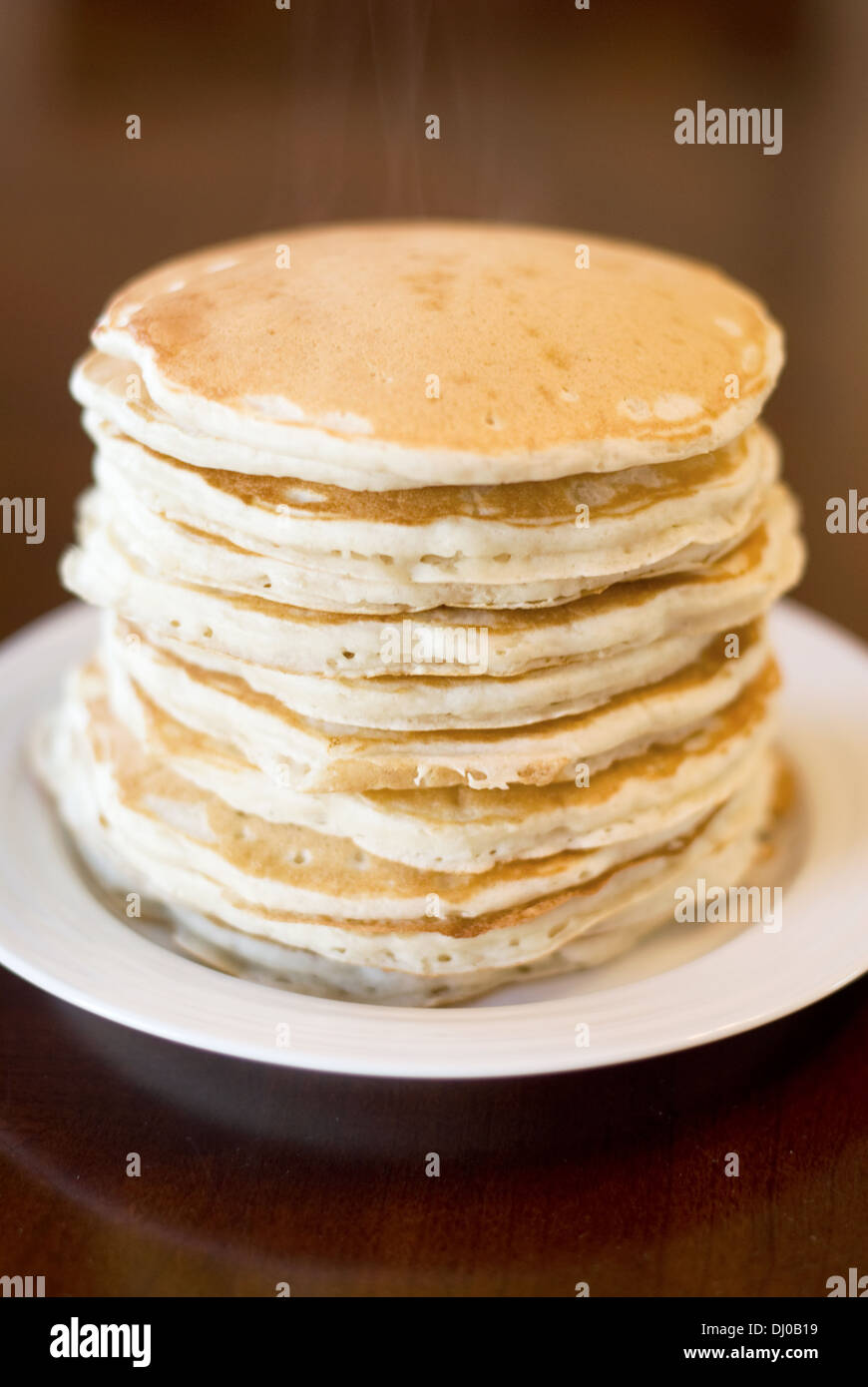 A stack of 10 fresh, hot buttermilk pancakes, with the steam still rising from the top. - Stock Image