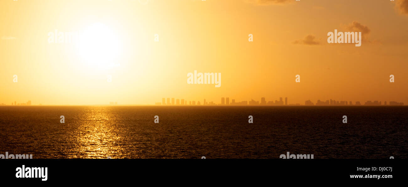 View of the setting sun over the ocean with the skyline of Miami, FL, USA in the distance. Stock Photo