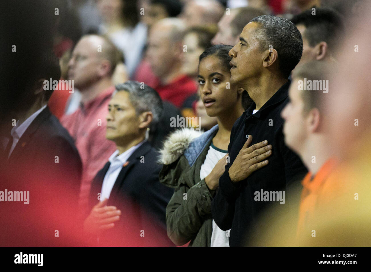 College Park, Maryland, USA. 17th Nov, 2013. (L-R): daughter Malia Obama and United States President Barack Obama stand during the National Anthem before the men's NCAA basketball match between University of Maryland and Oregon State University at the Comcast Center in College Park, Maryland, USA, 17 November 2013. Obama's brother-in-law Craig Robinson is the head coach of the Oregon State team. Credit: Drew Angerer / Pool via CNP/dpa/Alamy Live News - Stock Image