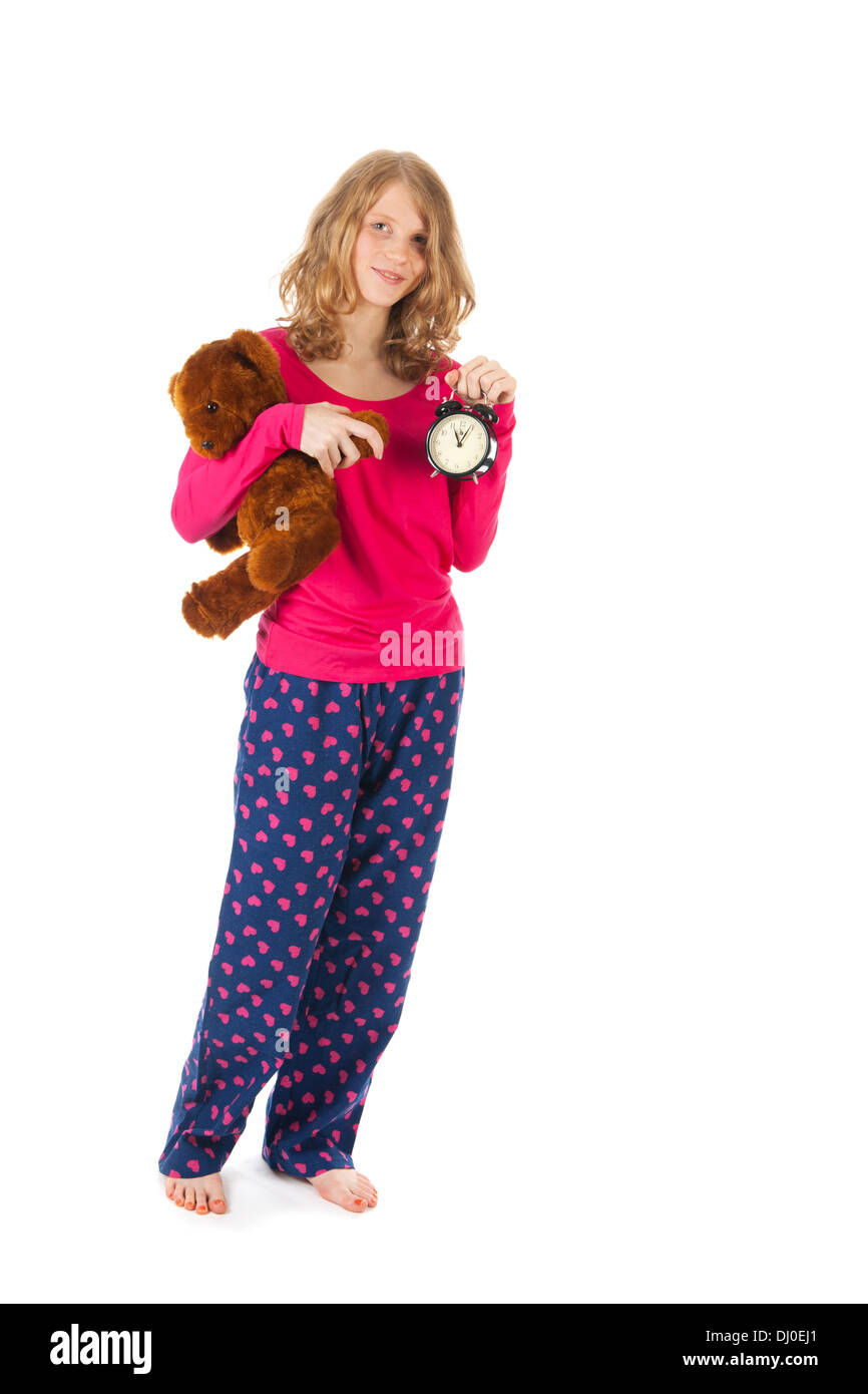 Young girl is going to bed with toy bear and alarm clock - Stock Image