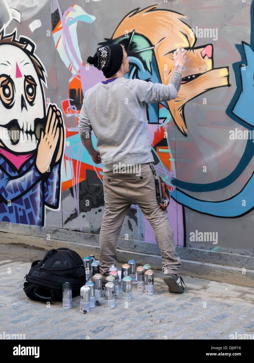 Graffiti artist at work in Brick Lane, east London - Stock Image