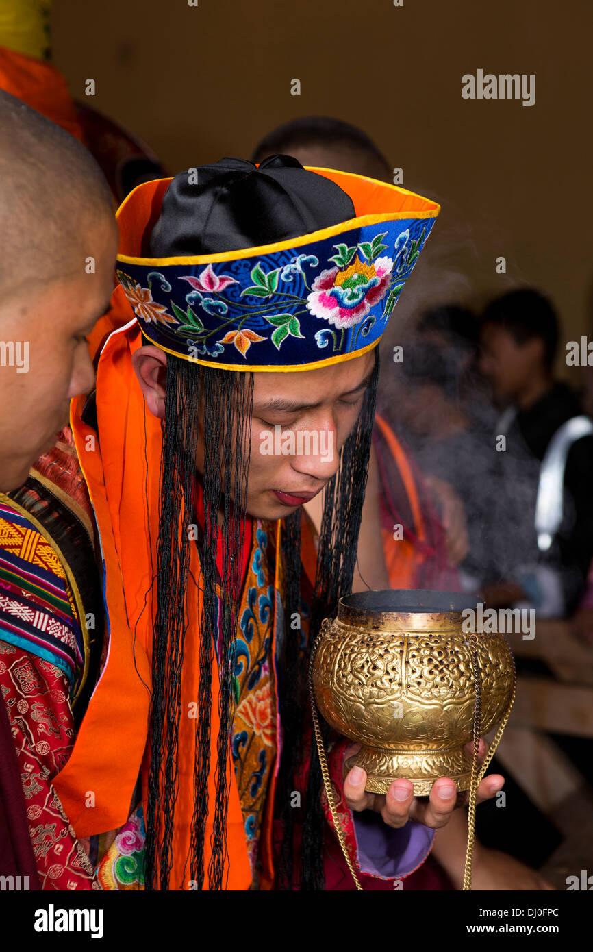 Bhutan, Thimpu Dzong, annual Tsechu, monk in embroidered costume lighting incense - Stock Image