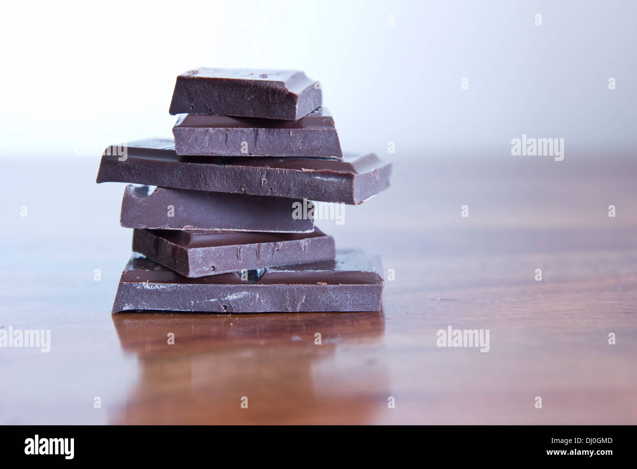 dark chocolate bars over wooden table - Stock Image