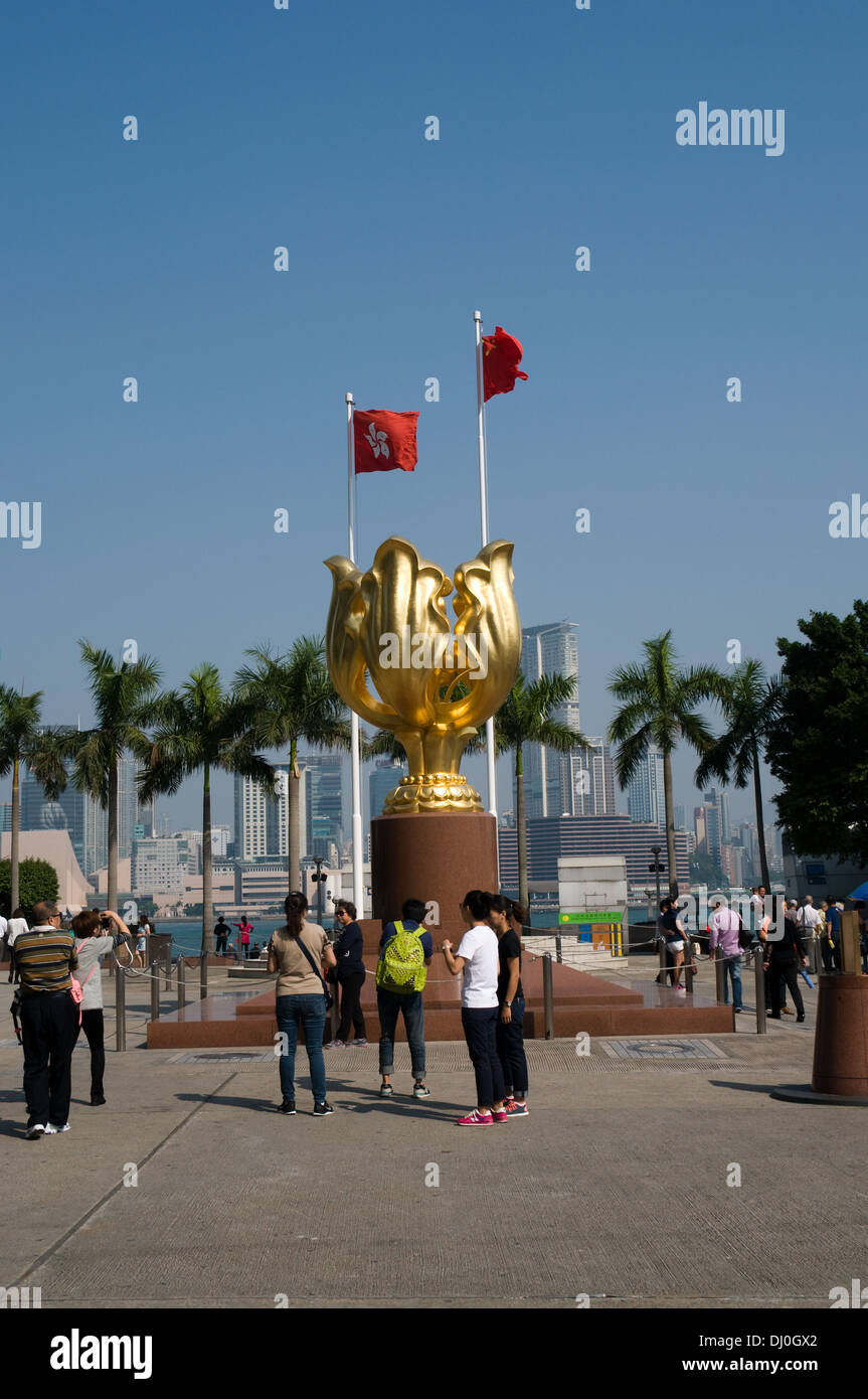 Tourists take pictures of the Forever blooming Bauhinai Scuplture that stands in front of the Hong Kong Convention center - Stock Image