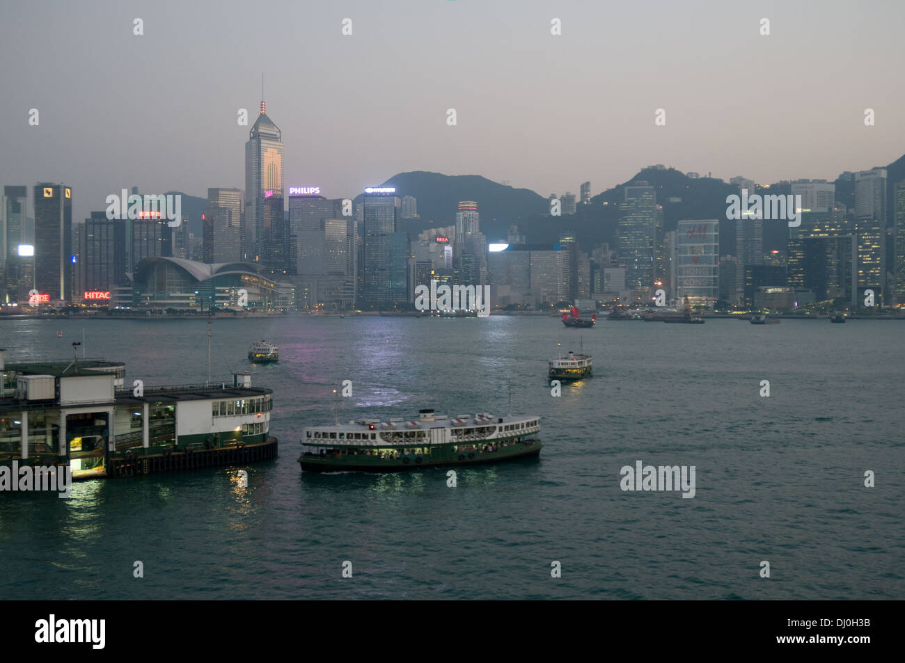 Star ferries come and go from the pier at Tsim Sha Tsui, Kowloon, Hong Kong S.A.R. Hong Island skyline in the background Stock Photo