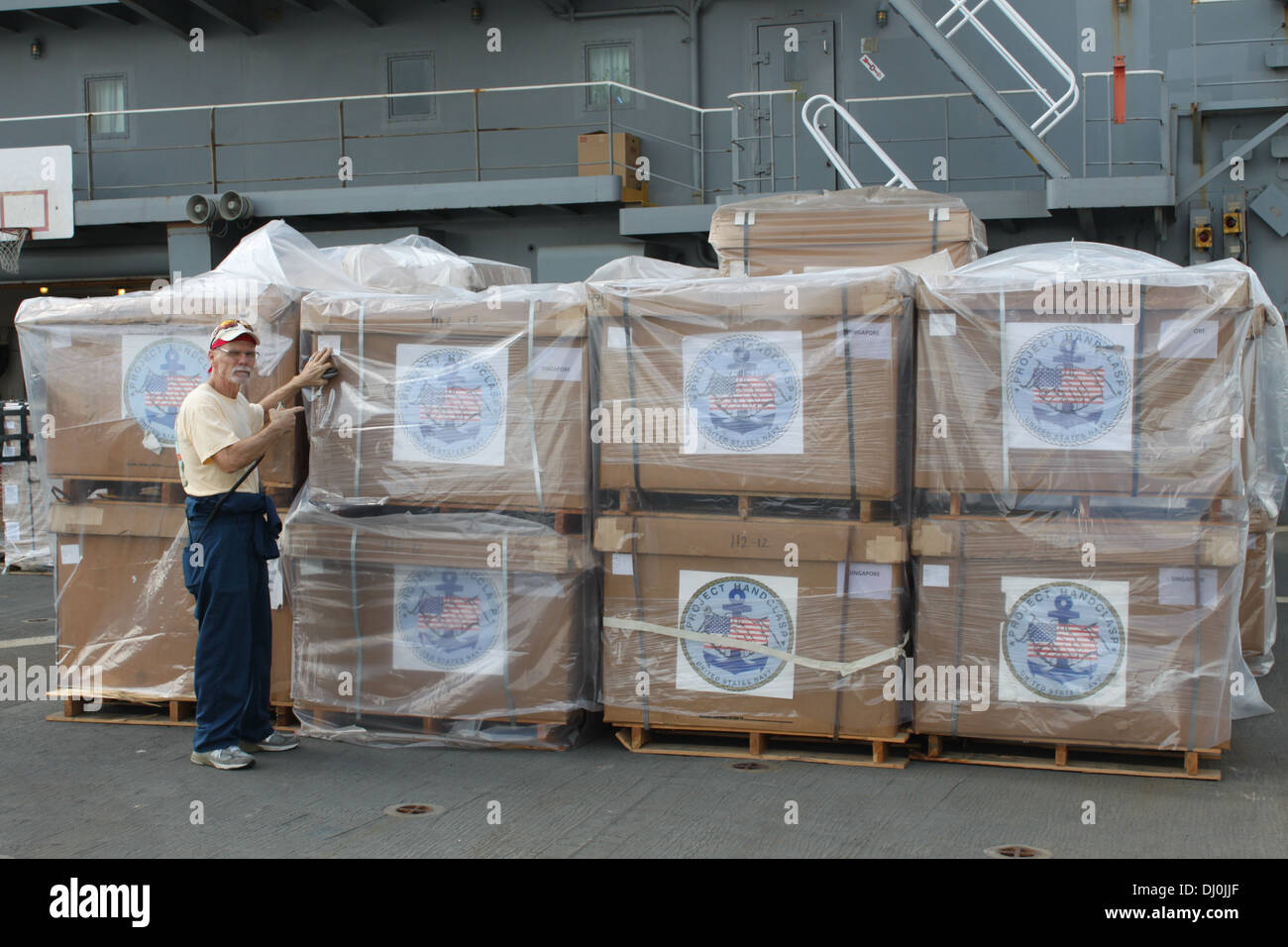 Civil service mariner Ron McCann, a supply officer assigned to the fleet replenishment oiler USNS Walter S. Diehl (T-AO 193), inspects cargo containing humanitarian supplies on the ship's flight deck at Sembawang Wharves in Singapore, Nov. 15, 2013, as pa - Stock Image