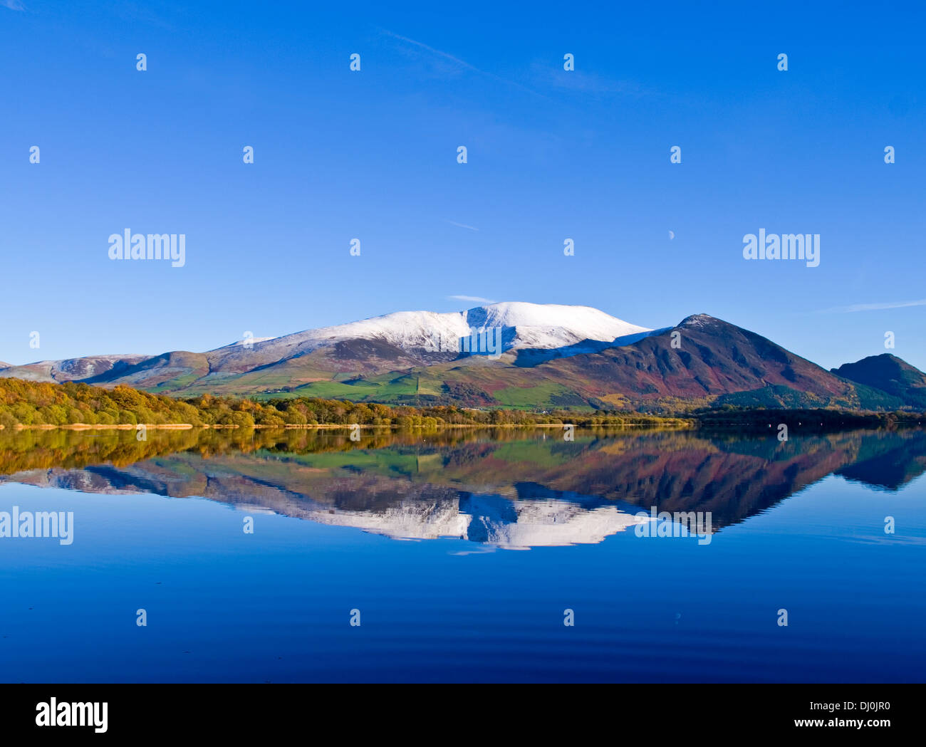 Snow-capped Skiddaw, Ullock Pike and Dodd reflected in the mirror-like Lake Bassenthwaite, Autumn, Lake District, Cumbria, UK - Stock Image