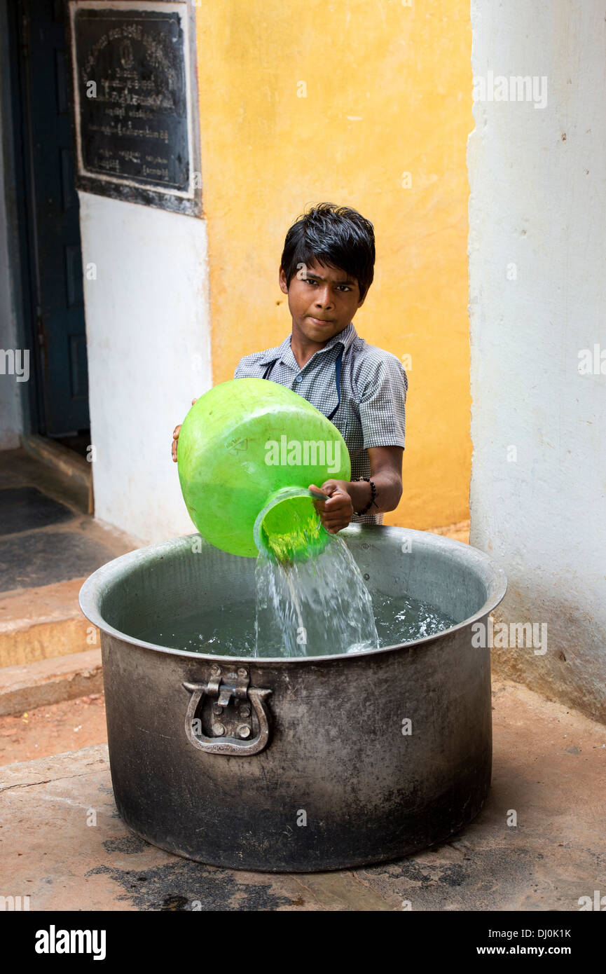Indian boy filling metal cooking pot with water in a rural Indian village street. Andhra Pradesh, India - Stock Image
