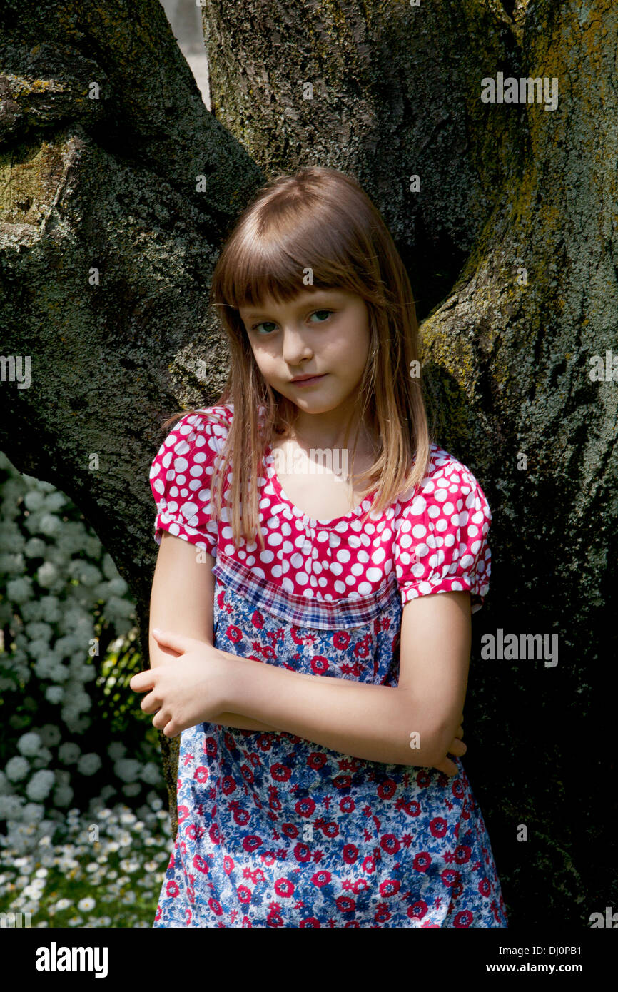 little girl leaning against a tree Stock Photo